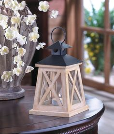 """This wooden candle lantern is the definition of classic country charm. White """"X"""" trim highlights the clear glass panels of this four-sided lantern, and the black roof features a hanging loop. Place the candle of your choice inside and enjoy the glow! Item Weight: 0.8 lb. 4 7/8 x 4 7/8 x 8 1/2 high. Wood, glass and iron."""