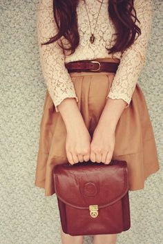 Vintage style. Long sleeved lace top, brown leather belt, skater skirt and brown leather satchel style bag.