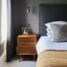 Sophisticated and smart, a muted scheme of strong greys and warm gold tones creates a cosseting feel in interior designer Emma Collins' bedroom. The headboard has been upholstered by Norris of blackheath and the walls are in Little Greene Dark Lead Absolute Matt Emulsion. Photograph by Jonathan Gooch