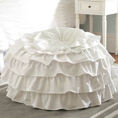 This from Pottery Barn--I have a simple round ottoman.  How simple to make a quick ruffly slipcover for it and get this look for my daughter!