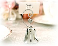"""Charming"" Silver Bell with Dangling Heart Charm  Let love ring with this ""charming"" bell placecard holder! The three-inch bell has a cleverly dangling heart and is crafted of fine silver chrome. Each bell is uniquely designed to hold a placecard or photo. The sound of ringing will fill your day, and the bell makes a special souvenir for your guests as they can hold their own cards and photos. Measures 3 1/2 x 1 3/4. #wedding #favors #weddingfavors #bell #placecards"