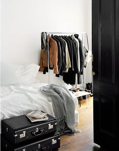 Maybe find some old suit cases and redo them to be all the same color and make a rolling clothes rack as well.