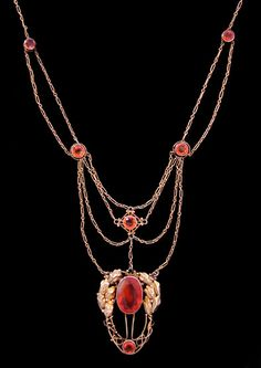 GLASGOW SCHOOL. ARTS & CRAFTS   A fine gold necklace. The openwork pendant with a facetted opal, flanked   by gold leaves and slender stems, with an opal drop below. The fine chains punctuated with further fire opals.  British circa 1900.