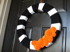 "Halloween wreath~ This is a cute, vintage way to tell your trick or treaters happy Halloween! This wreath is made out of styrofoam and is 18"" (perfect size for your front door!). The styrofoam wreath is wrapped with black and white yarn and has warm, fall felt flowers. Looks pretty easy to make."