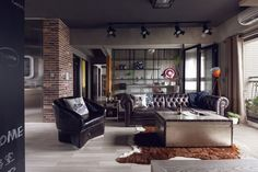 table basse style industriel en malle métallique dans le salon de style industriel avec murs de brique rouge, tapis en peau de vache et canapé Chesterfield