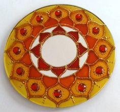 Mandala em espelho de 15cm de diâmetro, pintura vitral, decorado com tinta relevo dourada e pedrinhas acrílicas.  Mandala em sânscrito significa círculo. São veículos para o religamento da nossa consciência com o Todo Universal, do qual fazemos parte. As Mandalas além de decorativas servem para imprimir energias e trazer beleza ao ambiente em que se encontram.  O espelho é considerado um das 9 curas do Feng Shui. É usado para auxiliar na circulação da energia CHI em um ambiente. São muito…