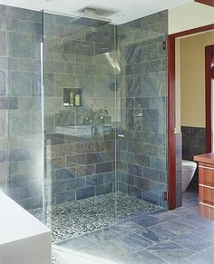 "Natural Materials - slate shower, glass door, stone floor. I could live with this!  ""Natural materials can add a masculine, earthy feel to baths. Here, dark slate flooring makes the crisp white tub and sink (not shown) pop. River stones are used in the shower and as a border around the freestanding tub to designate wet floor space."""