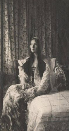 A rare photo of Tatiana Nikolaievna Romanov, daughter of Tsar Nicolas II taken at a happier time. She and her sisters were dressing up...just playing. Still, there is something haunting in this photo. The lighting...the faded photos in the background....