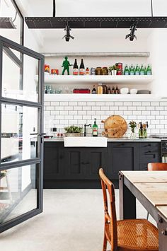 Kitchen: matt black cabinets, white farmhouse sink, zinc benchtop, white open shelving, white subway tile splashback with black grout, concrete floor, black steel-frame factory/warehouse-style glass door, black spotlights on ceiling-mounted track