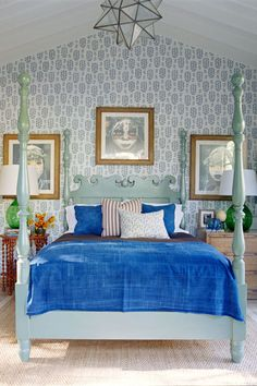 Designer Martyn Lawrence Bullard isn't afraid of color—and you shouldn't be either! A seafoam green four-poster bed pairs perfectly with a bright blue comforter and patterned wallpaper.