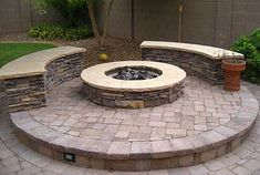 Ooooh! Look at this fire pit & curved bench combo...very nice because it's on a raised area. Install some lights underneath or inside the side walls of the bricks & it's even-more cool.