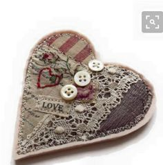 A gorgeous textile heart brooch. Perfect gift for a Valentine. Made from silk and cottons with lace and vintage buttons. A tiny hand embroidered red heart and backed with soft pale pink wool felt. The brooch comes presented on a tag tied with ribbon. Textile Jewelry, Fabric Jewelry, Textile Art, Jewellery, Fabric Hearts, Fabric Flowers, Lace Fabric, Valentines Day Hearts, Valentine Crafts