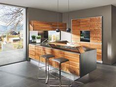 """Die Einbauküche """"Vao"""" stammt aus gutem Hause: TEAM 7 steht für einen natürlichen Look aus massivem Echtholz, der ebenso hochwertig wie ästhetisch ist. So haben Sie die idealen Voraussetzungen, um Ihren Freunden und Ihrer Familie leckere Gerichte im stilvollen Ambiente zu servieren. Entscheiden Sie sich beispielsweise für eine Front aus furniertem Nussbaumholz und runden Sie diese mit einem harmonischen Korpus ab. Die naturgeölte Oberfläche verleiht der Küche dabei eine geschmackvolle…"""