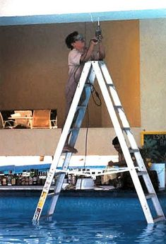 """Okay, sure, he's barefoot. On a metal ladder. In a pool. Working with power tools. But at least he's wearing his protective goggles!  This is called, """"Why women live longer than men."""""""