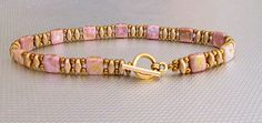 A fun and chic pink tila and gold super duo bracelet. This bracelet is very pretty. The tila beads resemble stones. This bracelet can be stacked with other bracelet or worn by itself with a nice dress or a t shirt and jeans. It is as unique as you are! It is 7 1/2 long. 14 K gold toggle. Treat yourself