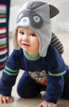 aw15: Elegant Baby's playful animal-themed accessories from Into the Woods, such as the Raccoon Hat, shown here with a coordinating knit jumpsuit, make whimsical gifts. www.elegantbaby.com