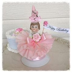 A sweet porcelain Birthday girl is all dressed in pink frills for her party. A vintage Birthday Month doll has a dress made with 3 layers of crepe paper