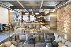 Cool idea of decorating a high ceiling studio apartment: u shaped sofa, industrial elements (lighting appliances and metallic units as well as the uncovered pipes) make a perfect home with keeping the old feel of the space given by the exposed bricks. Just breathe the airy space!!!
