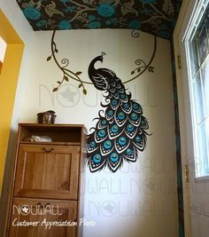 This giant decal is a unique way to add color and pattern to a wall. The colors in the wallpaper on the ceiling are also peacock-inspired.