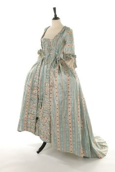 robe à la francaise, 1770s. Blue and white striped, figured and rose-sprigged silk satin, pleated an druffled robings edged in silk fly braid, petticoat with ruched furbelows.