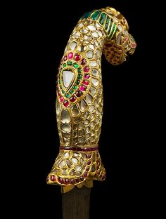 Dagger with a Yali Hilt Object Name: Dagger Date: ca. 1800 Geography: South India, Tanjore or Mysore Medium: Steel blade; gold hilt, inlaid with diamonds, rubies, and emeralds