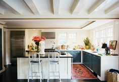 White cabinet boxes with blue door/drawer fronts. How unusual and cool. And I continue to love the look of lots of windows and no upper cabinets. Although I have way too many kitchen tools to make that work, I think.  Love the rug too. Helps complete the space.