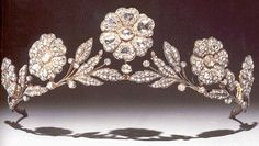 This is the Strathmore Rose Tiara. Lady Elizabeth Bowes-Lyon (the future Queen Elizabeth, the Queen Mother) received it as a gift from her father, the Earl of Strathmore, for her wedding in 1923. The piece itself is likely older than that; it may have already been an antique when the Earl purchased it. The tiara features a garland of wild roses in diamonds mounted in silver and gold. Suzy Menkes states in The Royal Jewels that the individual elements can be removed and worn separately.