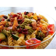 This pasta salad with cucumber, tomato, and bell pepper is topped with bacon bits and dried cranberries.