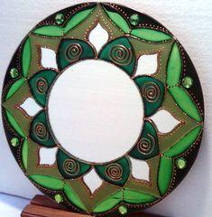 Espelho 25cm de diâmetro, técnica em vitral, decorado com pedras em acrílico verde e tinta relevo dourada.   Mandala em sânscrito significa circulo. Elas têm a propriedade de nos prender a atenção, de nos convidar a introspecção. Observando sua simetria nos tranqüilizamos, propiciando a Mente a se distanciar dos problemas imediatos, induzindo ao exercício da contemplação. São veículos para o religamento de nossa consciência com a fonte absoluta de onde provimos e que constituem todo o…