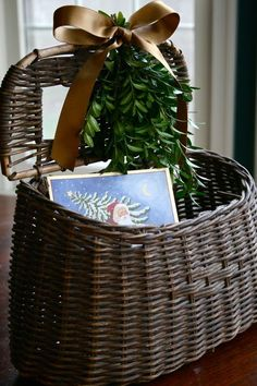 Love this boxwood with a bow decorated fishing basket to keep Christmas cards in.