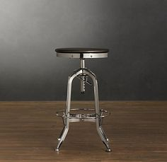 Toledo Barstool Polished Chrome $345 Our perfect reproduction of the classic vintage draftsman's stool pairs industrial steel with the warmth of wood seating. Bent steel base is constructed with a spring-loaded clamp and steel pole for height adjustment Heavily distressed base Chrome with distressed black-finished wood seat  This collection is designed for residential use This item is artisan crafted with meticulous care. Given its handmade and hand-finished nature, variations in the…