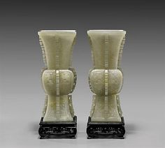"""Estimated Price: $24,000 - $28,000  Description: PAIR CARVED WHITE JADE GU VASES Pair of fine, Chinese carved white jade vases; of archaistic gu-form, each decorated with interlocking geometric patterning, with notched ribs running along the center of each side; the jade of translucent yellowish-white coloration; H: 8 1/4"""" (each); wood stands"""