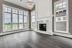Living room inspiration, center fireplace between windows, white trim work and marble, grey wood floors, neutral living room, chandelier living room