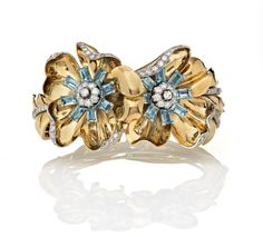 A Gold, Diamond and Aquamarine Bracelet by Paul Flato, Circa 1955, United States, centred by two flower heads set with diamonds and baguette cut aquamarines, with stylised gold and diamond leaves. One of the flowers detatches as a clip.