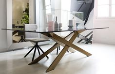 The elegance and #design of CROSS #table with burnished metal base and bronzed #glass top.