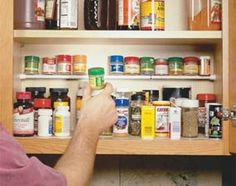 use a small tension rod to store the short, tiny spice bottles . .. This site has lots of great storage ideas!