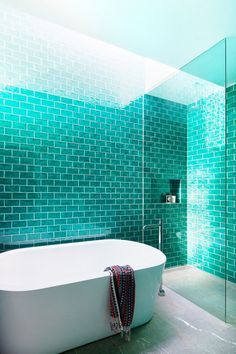 A modern bathroom with floor to ceiling teal tiles, and a freestanding bathtub