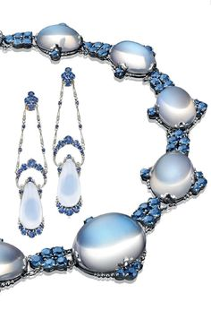 LOUIS COMFORT TIFFANY, TIFFANY & CO. - AN MOONSTONE AND SAPPHIRE DEMI PARURE, CIRCA 1910. Comprising a necklace, designed as a series of graduated oval-shaped moonstone cabochons, trimmed by circular-cut sapphires, joined by circular-cut sapphire cluster links; and a pair of ear pendants en suite, mounted in platinum. Each signed Tiffany & Co. #LouisComfortTiffany