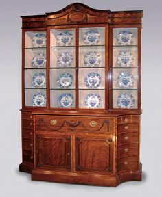 An important Mid 18th Century padouk/pallisander Breakfront Bookcase in the manner of Mayhew & Ince, having moulded & arched double top with vitruvian scroll, ribbon & swag satinwood inlaid cornice, centred with oval panel & similar ribbon & husk carving, above glazed doors enclosing later silk lining & glass shelves. The base, kingwood crossbanded throughout, fitted with secretaire drawer with boldly carved urn & swag decoration. Circa: 1785 Ref: 4740