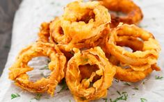 In the Spicy Indian Style Onion Rings the flavor of the onion rings is spiked up by using ginger, garlic and chilies. They are spicy, zesty and make a good addition to a chaat-party or tea party menu. Crispy Onions, Fried Onions, Tempura, Blooming Onion Sauce, Beer Battered Onion Rings, Onion Rings Recipe, Snack Recipes, Cooking Recipes, Drink Recipes