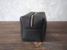 Handmade Leather Dopp Kit. Black color. Cut and pierced by hands. Moreover, it's sewn by hands but not with a machine, what makes it even more precious. Your initials or other information can be added with stamping method. SIZES: W*H*L 110*105*200 mm, (4,3*4,1*7,8 in) Genuine leather, 2