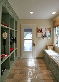Pastel colored mudroom. Adorable green and cream color layout. This is a great place for the family members to put their shoes coats cats and backpacks. Gray tiles are easy to clean.