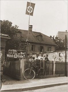 Young Nazi party supporters stand next to an election poster that reads -Adolf Hitler will provide work and bread!