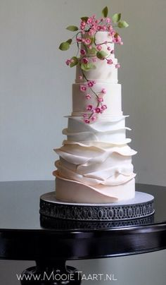 Elegant blush cake with pink blossoms.