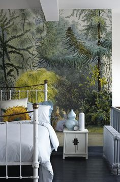 a painted iron bed, a sunflower cushion and a forest mural