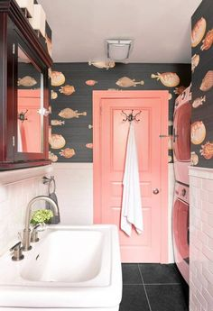 Give your bathroom a splash of color with this coral pink tile + patterned wallpaper.