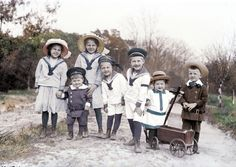 A group of Edwardian era children in sailor suits on the beach