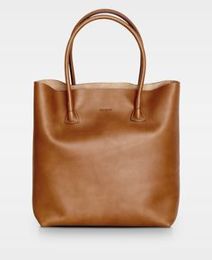 369 plain tote in cognac is a tote bag made of full grained leather with a natural, smooth structure. This bag has no lining but a small leather compartment inside. It is a reinterpretation of our iconic 104 Working bag. The tote is perfect for everyday u Smooth Leather, Bag Making, Cross Body, Kylie, Madewell, Elsa, Shoulder Strap, Totes, Tote Bag