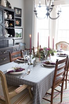 A perfect Thanksgiving table setting using a modern gray tablecloth, brass candlesticks and an ironstone floral centerpiece with privet berries, pepper berries, olive branches, kale and eucalyptus. @findinghome