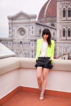 Love her neon blazer and feminine shorts.